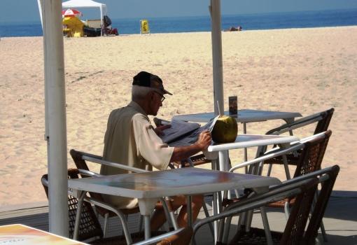 Brasileiro lendo com café da mnhã, praia 1603